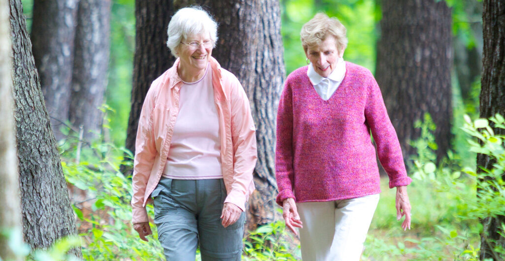Two active independent living residents of RiverWoods Exeter hiking in the woods in Exeter, New Hampshire.